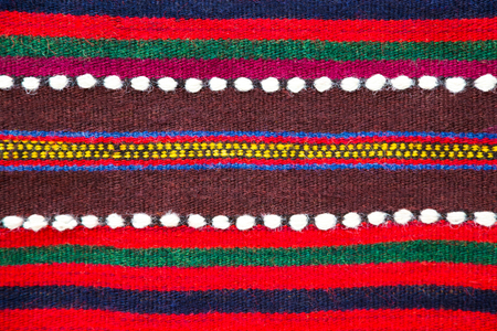 rug texture: Colorful handmade Bulgarian woollen rug with a striped pattern in red, green and burgundy with white dotted accents, close up view in a full frame background pattern and texture Stock Photo