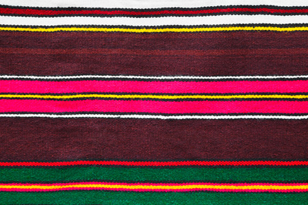 rug texture: Background pattern and texture of a handmade woollen rug with colorful stripes over a dark burgundy background in a full frame view Stock Photo