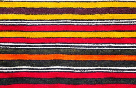 rug texture: Multicolored handmade woollen rug texture with parallel stripes in red, yellow, black, white and orange in a closeup full frame view