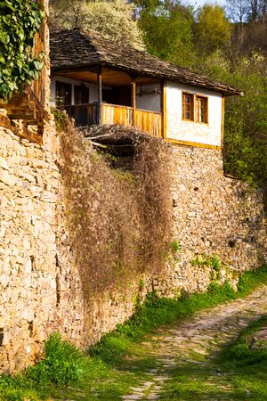real renaissance: Quaint old traditional stone house in Leshten village in the Rhodope mountains in Bulgaria with a stone retaining wall below Stock Photo