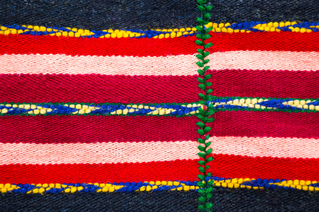 rug texture: Brightly colored Bulgarian woven handmade woollen rug texture with a red and white stripes decorated with blue, yellow and green patterns in a fill frame detailed view Stock Photo