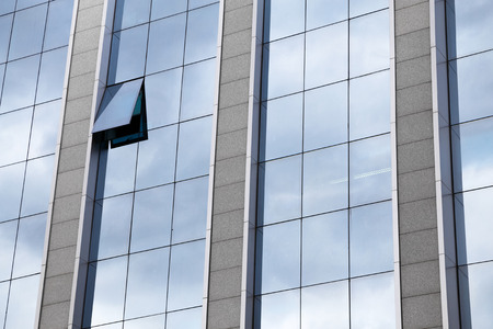 windowpanes: External facade of a modern glass fronted office block with one single window raised and open in a full frame architectural background Stock Photo