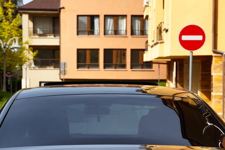 block of flats: Car with dark tinted windows in an urban street below colorful apartment blocks and a no entry sign, close up view of the windshield Stock Photo