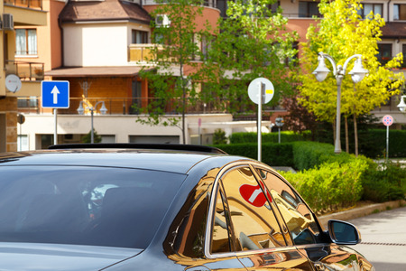 coachwork: Car with dark tinted windows driving down a residential urban street with apartment blocks and multi-storey houses with a no entry sign reflected in the glass