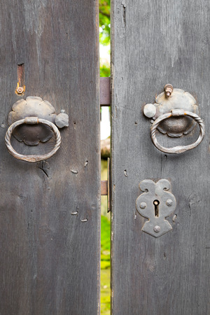 old wooden door: Two old iron ring handles and lock on an old weathered wooden door standing ajar showing a glimpse of a garden Stock Photo