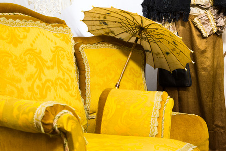 Unique background of old fashion arm chair with yellow upholstery and parasol placed beside it by vintage clothing hanging against wall Stock Photo