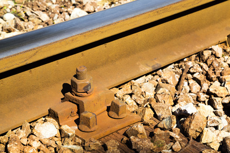 receding: Close up detail of a rail track showing the steel track mounted on wooden sleepers in gravel with rusty bolts in a travel and transport concept Stock Photo