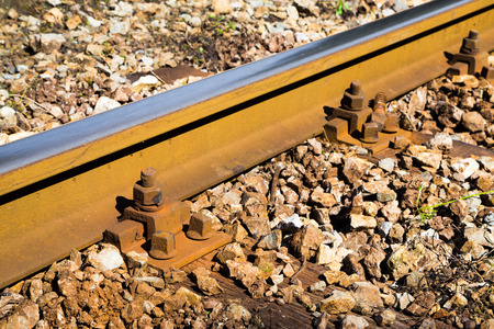 rail track: Close up detail of a rail track showing the steel track mounted on wooden sleepers in gravel with rusty bolts in a travel and transport concept Stock Photo