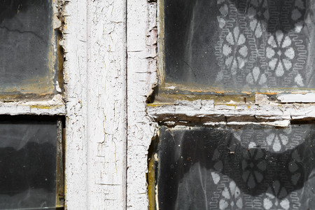 Close up view of an old exterior window frame with cracked and chipping white paint as lacy curtains hang behind it 版權商用圖片 - 69438013