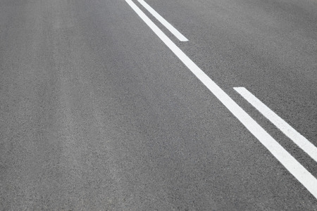 overtaking: Abstract close up image of paved road with black tarred surface and white painted dividing lines to indicate driving lanes