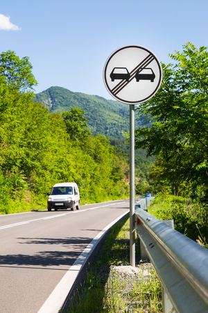 overtaking: End of overtaking prohibition road traffic sign on a signpost at the side of a mountainous road with an approaching white car