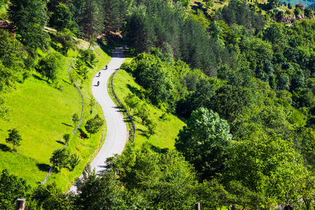 forested: Aerial view of three motorcyclists on a winding rural road through a scenic lush green forested mountain valley