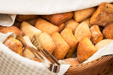 Basketful of ciabatta bread wirh a pair of serving tongs in a cloth lined wicker basket on a buffet table or bakery
