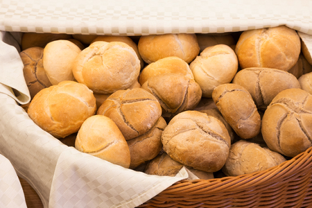 accompaniment: Wicker basket lined with a cloth filled with freshly baked crusty white buns with a star pattern in a close up high angle view Stock Photo