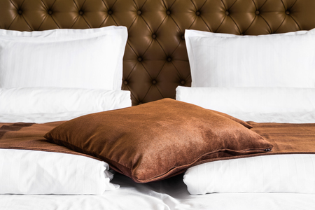 throw up: Brown cushion lying on a throw rug over a white duvet on a stylish double bed with upholstered brown headboard, close up view