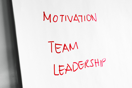 angled: Close up on angled view of the words Motivation, Team and Leadership in red marker on paper for business or education concept