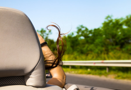 top down car: Woman riding in a sports car or cabriolet with the top down viewed from behind with her arm hanging out past the leather head rest and hair blowing in the breeze Stock Photo
