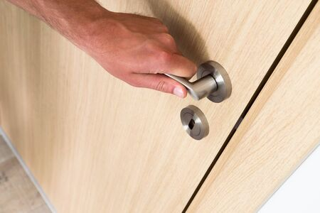shutting: Man opening a light hardwood wooden household door with a close up view of his hand on the handle above a circular keyhole and lock, high angle oblique view with copy space Stock Photo