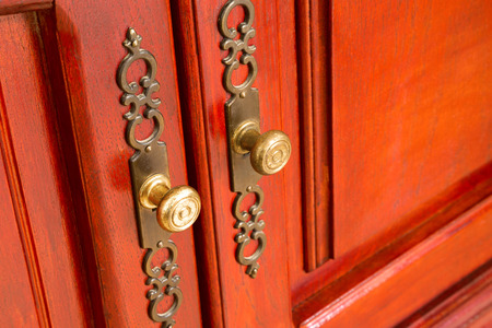 Brass door handles with ornate escutcheons on a wooden cabinet or cupboard with raised panels, close up oblique angle view with copy space