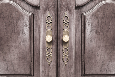 close fitting: Stylish brass door handles on a hardwood cabinet or closet with ornate escutcheons and raised panels on the doors in a close up frontal view conceptual of furnishing and interior decor Stock Photo