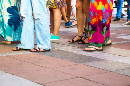 socialising: Group of casual men and women standing on paving in a low angle view of their feet in sandals, jeans, shorts and caftans or long summer skirts, with foreground copy space Stock Photo