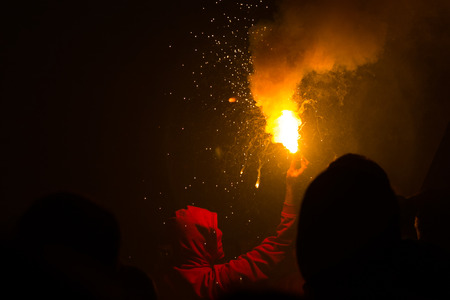 ultras: Hooded person holding torch for protest, celebration or football game in dark area with others watching Stock Photo