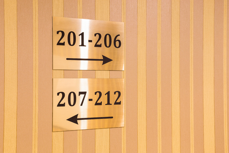 striped wallpaper: Gold metallic hotel sign with room numbers and arrows pointing in two opposite directions showing the way on a wall with striped wallpaper in a concept of travel