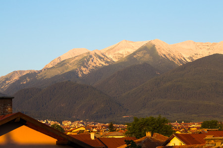 Morning sunrise view in glowing light of the Pirin Mountain and rooftops of the town of Bansko in summer, a popular Bulgarian ski resort and tourist destination