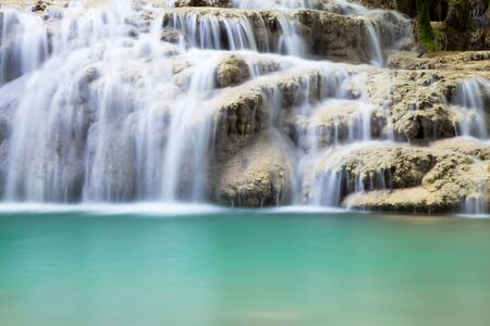 Waterfall cascading over a shelf of rocks into a quiet pool below in a long exposure nature background with veils of white water Stock Photo