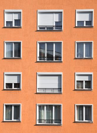 urban housing: Exterior of modern light orange or ocher urban housing block with apartments Stock Photo