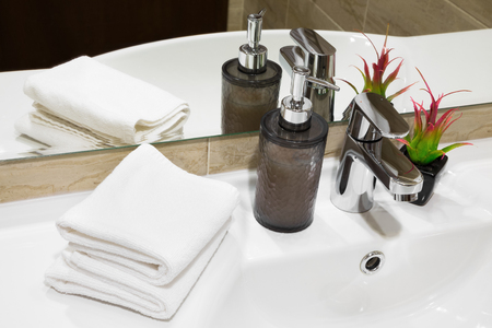 Stylish liquid soap pump and potted flowering plant on a white hand basin with clean towels in a hotel or home, high angle close up view Stock Photo