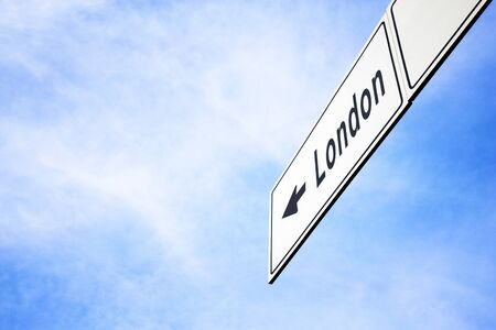 White signboard with an arrow pointing left towards London, England, United Kingdom, the capital city, against a hazy blue sky in a concept of travel, navigation and direction