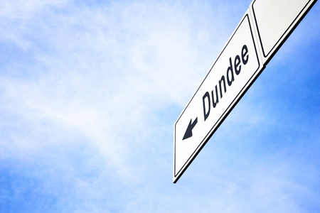 White signboard with an arrow pointing left towards Dundee, Scotland, United Kingdom, against a hazy blue sky in a concept of travel, navigation and direction. Path included for the signboard Stock Photo