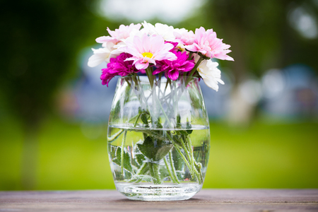 Decorative posy of fresh pink summer flowers in a glass vase on an outdoor wooden table viewed close up on the side Stock Photo