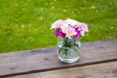 Colorful pink summer flowers in a glass vase outdoors on a rustic wooden garden table with copy space over green grass Stock Photo