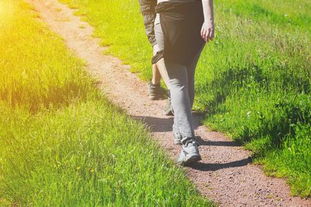 彼らは、隅に太陽の輝きを持つ緑豊かな緑の草を自然の中の日当たりの良い春の日ハイキングを楽しむ田舎のトラックに沿ってカメラから離れて歩