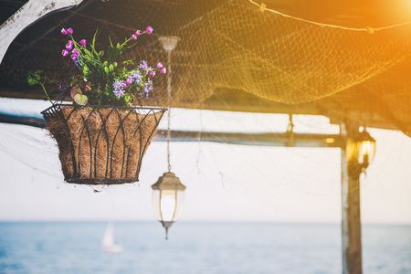 Beautiful hanging basket with artificial flowers hooked on a wooden shelter on the sea shore against a nice blurred sea with the glow of the sun in the corner