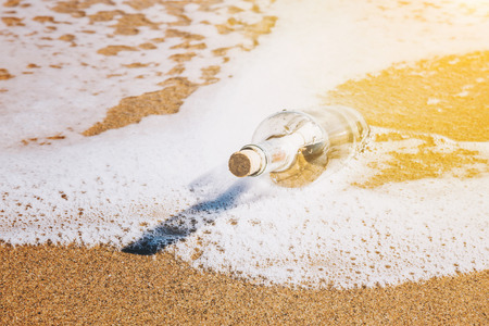 Message in a bottle washed up by the sea lying half submerged in the golden beach sand on the edge of the surf in a conceptual image of romance or a shipwreck with the glow of the sun in the corner