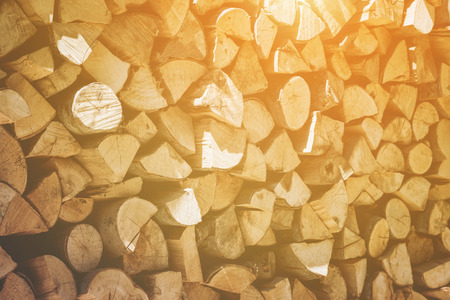 Background texture of a neatly stacked woodpile of dried, cut and split logs for providing winter heating and fuel in a full frame and diagonal view with the sun glow in the right corner