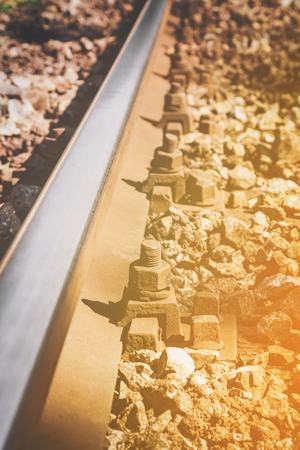 Close up view of steel railroad track with corroded metal bolts and surrounded by aged stones with the sun glow in the lower right corner