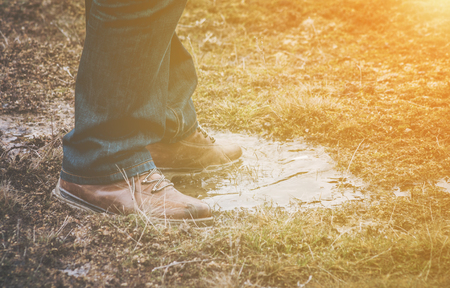Feet of a person wearing lace up shoes and blue denim jeans standing in a puddle of water in short scrubby grass with golden glow from the sun Stock Photo