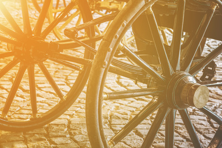 Details of old vintage carriage wheels at the street with golden glow from the sun
