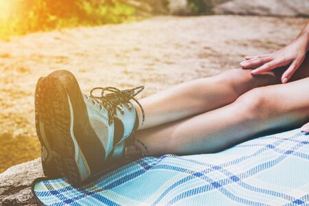 Close up of young woman bare legs with shoes laying outdoors on blue plaid blanket for theme about resting after a long day hiking with golden glow from the sun