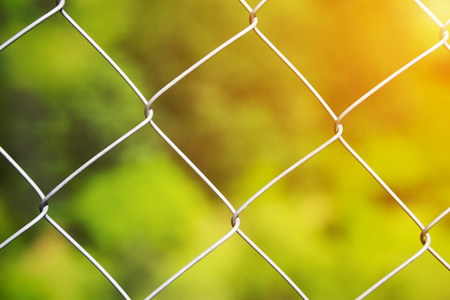 Detail of a diamond mesh wire fence with selective focus to the steel wire over a blurred green background with golden glow from the sun Stock Photo