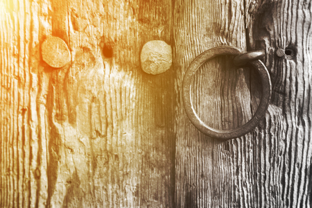 Old rustic weathered wooden door with a wrought iron ring handle and large old studs or nails, close up background texture with golden glow from the sun. Banque d'images