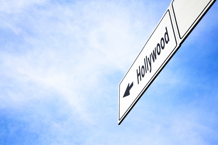 White signboard with an arrow pointing left towards Hollywood, Florida, USA, against a hazy blue sky in a concept of travel, navigation and direction. Path included for the signboard