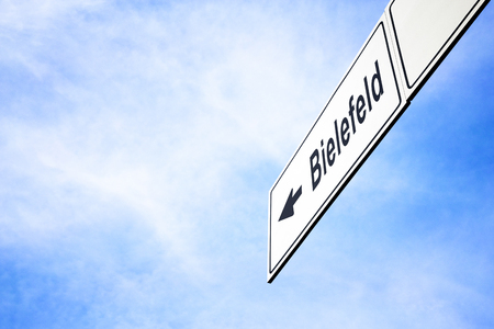 White signboard with an arrow pointing left towards Bielefeld, North Rhine-Westphalia, Germany, against a hazy blue sky in a concept of travel, navigation and direction. Path included
