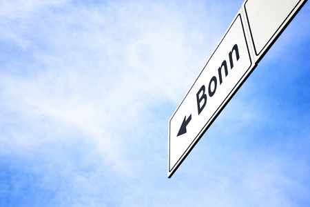 White signboard with an arrow pointing left towards Bonn, North Rhine-Westphalia, Germany, against a hazy blue sky in a concept of travel, navigation and direction. Path included for the signboard 스톡 콘텐츠