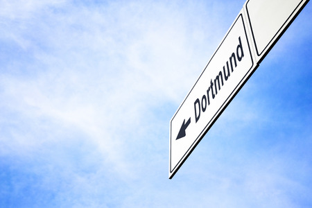 White signboard with an arrow pointing left towards Dortmund, North Rhine-Westphalia, Germany, against a hazy blue sky in a concept of travel, navigation and direction. Path included for the signboard 스톡 콘텐츠