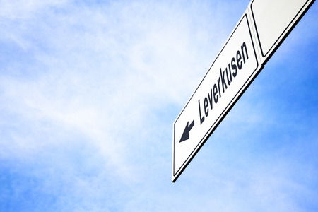 White signboard with an arrow pointing left towards Leverkusen, North Rhine-Westphalia, Germany, against a hazy blue sky in a concept of travel, navigation and direction. Path included